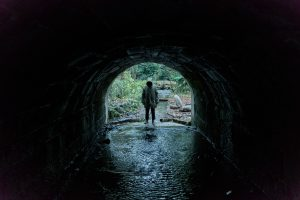 a hooded man at the edge of a tunnel over a water way