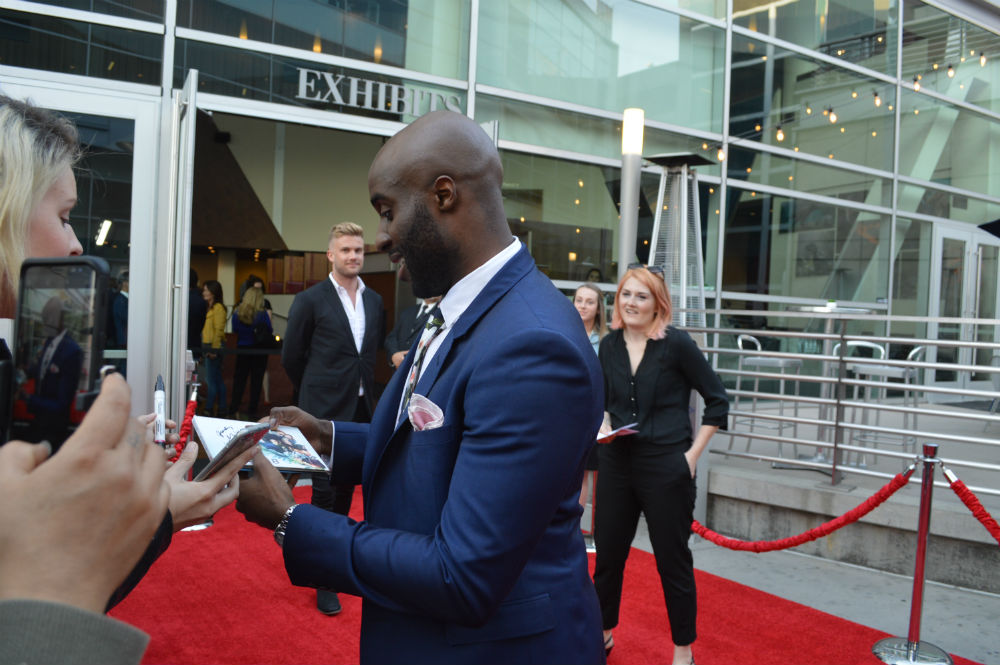Toby Onwumere signing autographs for fans.